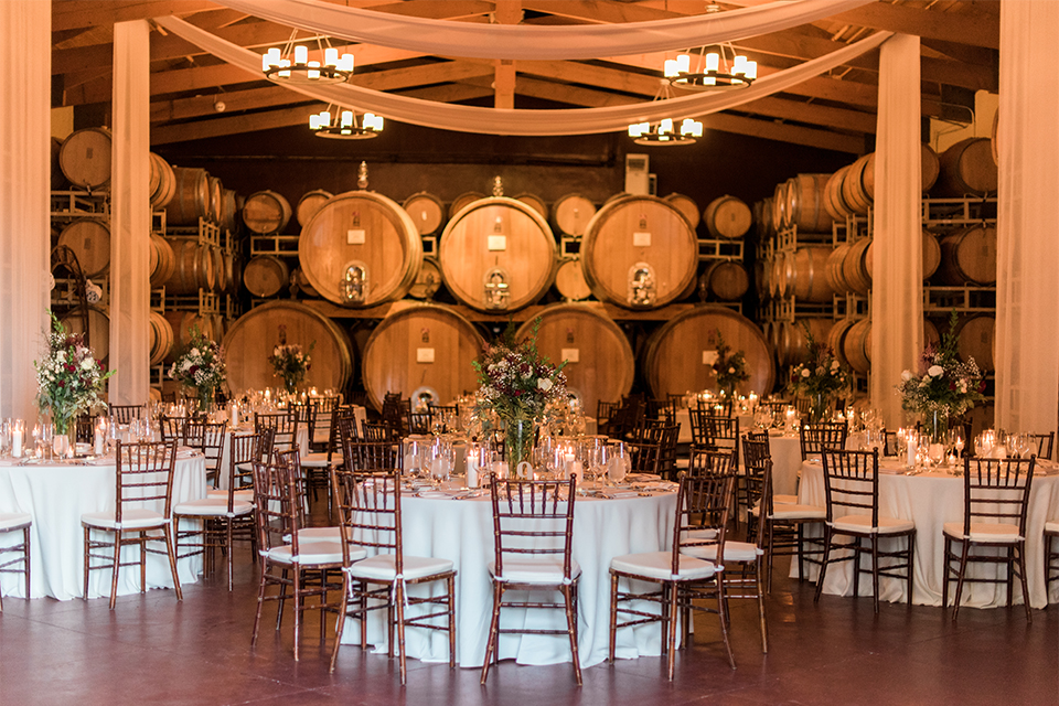 Temecula outdoor wedding at ponte winery reception set up with white table linen and dark chairs with white and green flower centerpiece decor with wine barrels along walls and gold candle decor with wine glasses