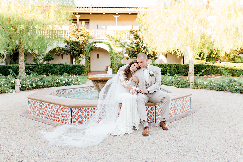 Temecula outdoor wedding at ponte winery bride form fitting lace gown with long sleeves and illusion open back design with sweetheart neckline and groom tan suit with matching vest and white dress shirt with matching tan bow tie and white floral boutonniere sitting by fountain