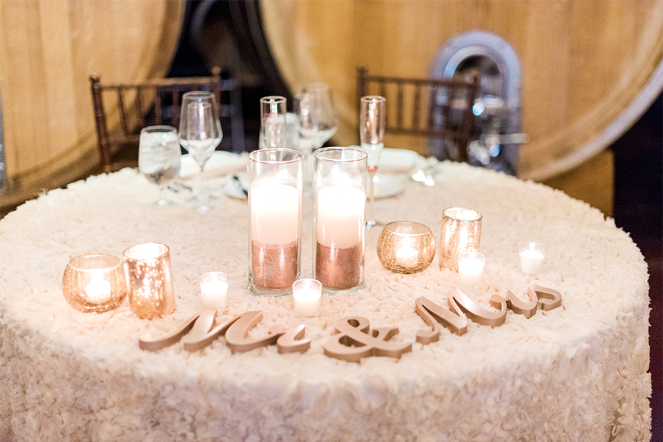 Temecula outdoor wedding at ponte winery reception set up with white table linen and dark chairs with white and green flower centerpiece decor with wine barrels along walls and gold candle decor with wine glasses mr and mrs sign for sweetheart table