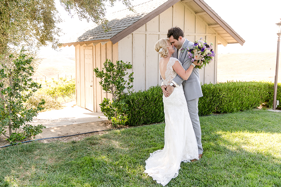 Temecula outdoor wedding at callaway winery bride form fitting lace gown with thick straps and open back design with plunging neckline with groom heather grey suit with matching vest and white dress shirt with long ivory tie and purple floral boutonniere hugging