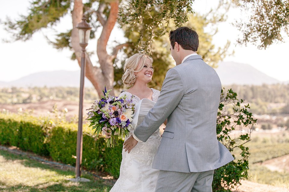 Temecula outdoor wedding at callaway winery bride form fitting lace gown with thick straps and open back design with plunging neckline with groom heather grey suit with matching vest and white dress shirt with long ivory tie and purple floral boutonniere first look hugging