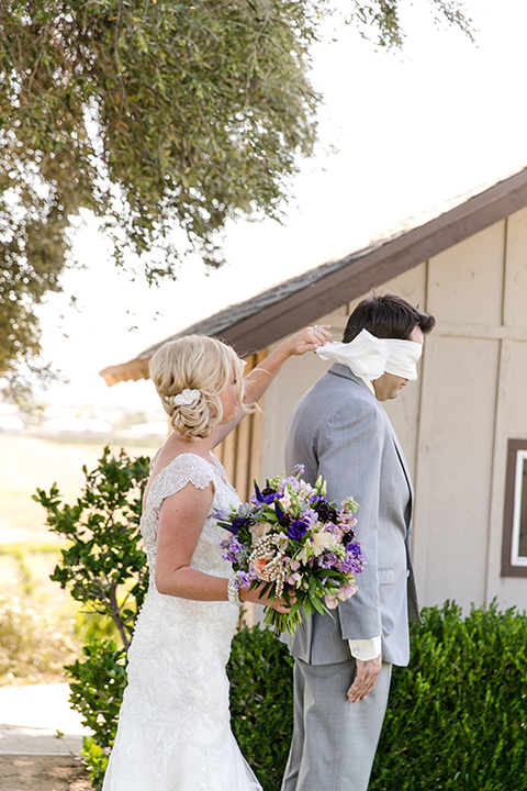 Temecula outdoor wedding at callaway winery bride form fitting lace gown with thick straps and open back design with plunging neckline with groom heather grey suit with matching vest and white dress shirt with long ivory tie and purple floral boutonniere first look unwrapping blindfold