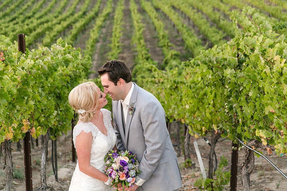 Temecula outdoor wedding at callaway winery bride form fitting lace gown with thick straps and open back design with plunging neckline with groom heather grey suit with matching vest and white dress shirt with long ivory tie and purple floral boutonniere kissing bride holding white and purple floral bridal bouquet