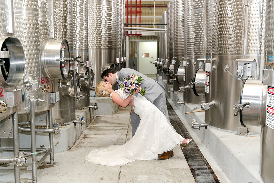 Temecula outdoor wedding at callaway winery bride form fitting lace gown with thick straps and open back design with plunging neckline with groom heather grey suit with matching vest and white dress shirt with long ivory tie and purple floral boutonniere kissing