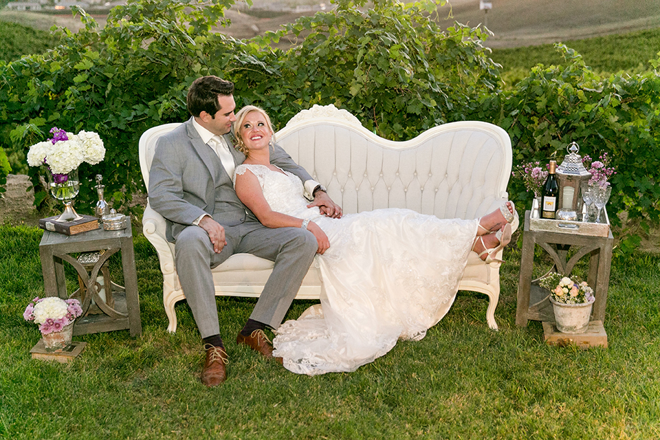 Temecula outdoor wedding at callaway winery bride form fitting lace gown with thick straps and open back design with plunging neckline with groom heather grey suit with matching vest and white dress shirt with long ivory tie and purple floral boutonniere sitting on couch
