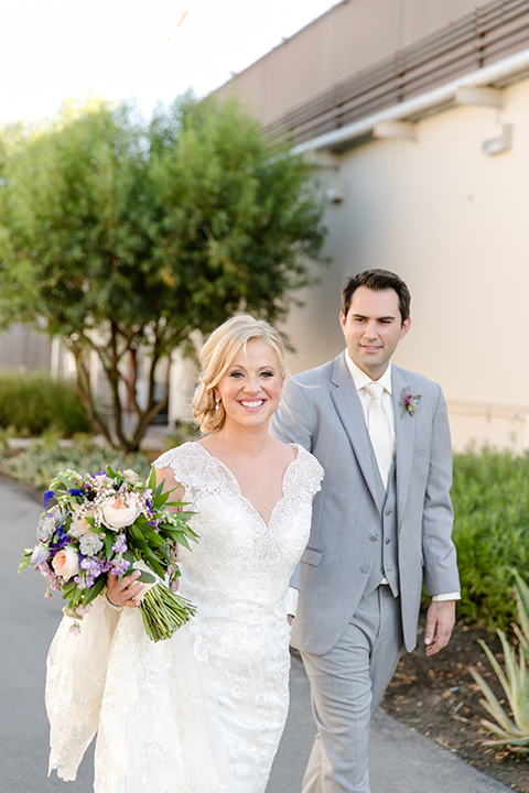 Temecula outdoor wedding at callaway winery bride form fitting lace gown with thick straps and open back design with plunging neckline with groom heather grey suit with matching vest and white dress shirt with long ivory tie and purple floral boutonniere holding hands bride holding white and purple floral bridal bouquet