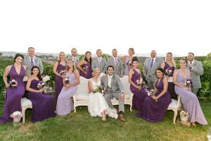 Temecula outdoor wedding at callaway winery bride form fitting lace gown with thick straps and open back design with plunging neckline with groom heather grey suit with matching vest and white dress shirt with long ivory tie and purple floral boutonniere sitting down with wedding party bridesmaids long purple dresses and groomsmen heather grey suits with long purple ties