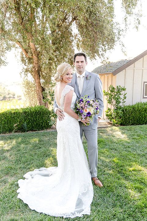 Temecula outdoor wedding at callaway winery bride form fitting lace gown with thick straps and open back design with plunging neckline with groom heather grey suit with matching vest and white dress shirt with long ivory tie and purple floral boutonniere hugging bride holding white and purple floral bridal bouquet