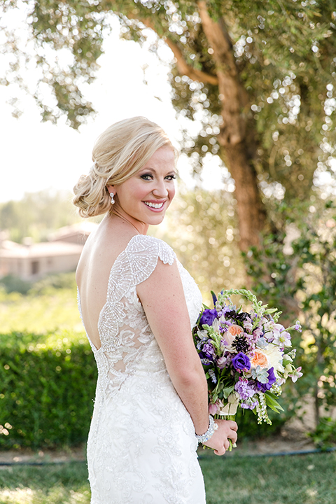 Temecula outdoor wedding at callaway winery bride form fitting lace gown with thick straps and open back design with plunging neckline with white and purple floral bridal bouquet