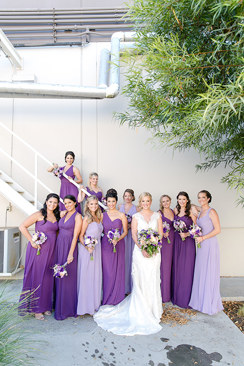 Temecula outdoor wedding at callaway winery bride form fitting lace gown with thick straps and open back design with plunging neckline with white and purple floral bridal bouquet with bridesmaids long purple dresses with white and purple floral bridal bouquet