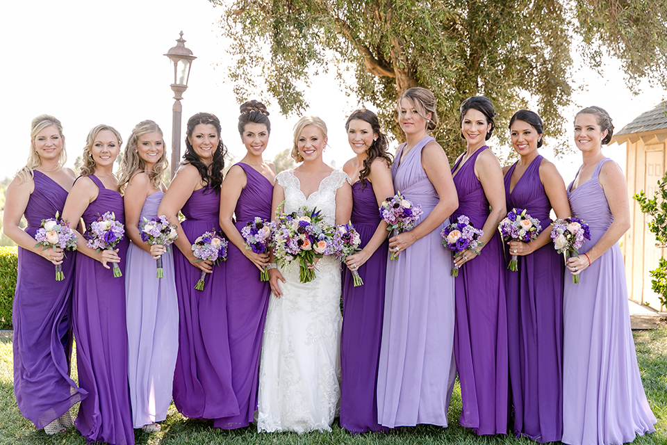 Temecula outdoor wedding at callaway winery bride form fitting lace gown with thick straps and open back design with plunging neckline with white and purple floral bridal bouquet with bridesmaids long purple dresses with white and purple floral bridal bouquets
