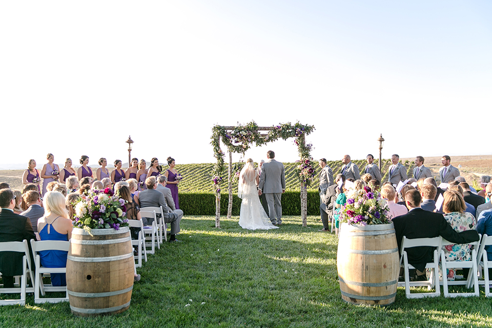 Temecula outdoor wedding at callaway winery bride form fitting lace gown with thick straps and open back design with plunging neckline with groom heather grey suit with matching vest and white dress shirt with long ivory tie and purple floral boutonniere holding hands during ceremony