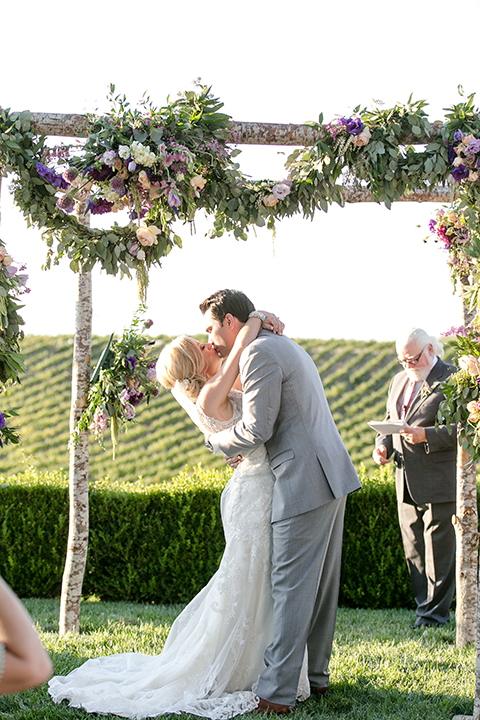 Temecula outdoor wedding at callaway winery bride form fitting lace gown with thick straps and open back design with plunging neckline with groom heather grey suit with matching vest and white dress shirt with long ivory tie and purple floral boutonniere kissing during ceremony