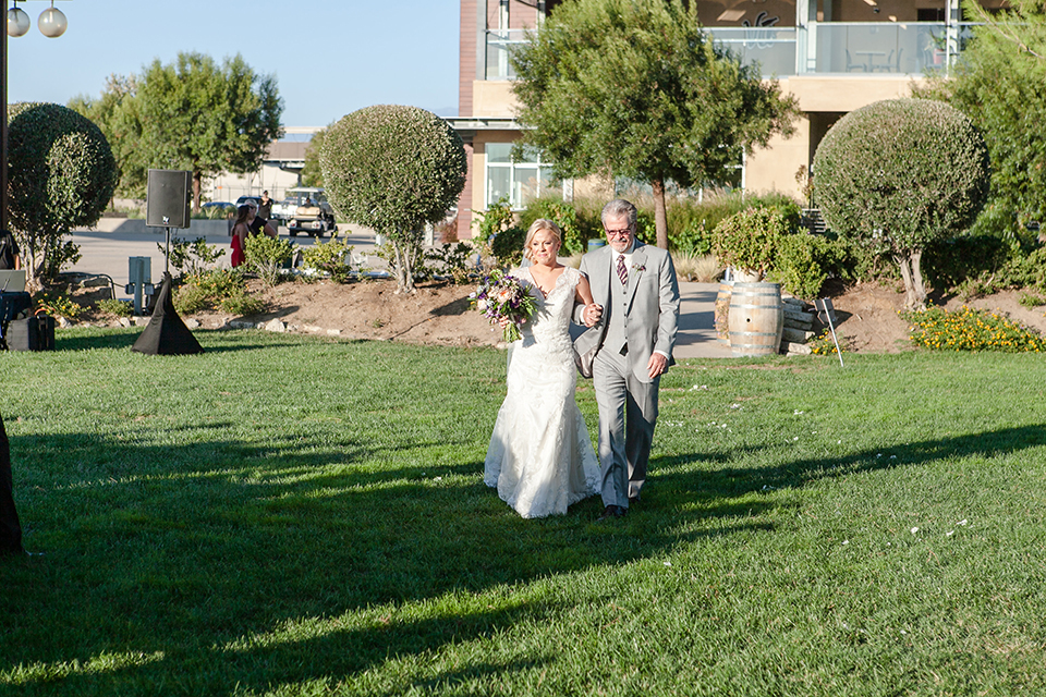 Temecula outdoor wedding at callaway winery bride form fitting lace gown with thick straps and open back design with plunging neckline with white and purple floral bridal bouquet walking down the aisle with dad