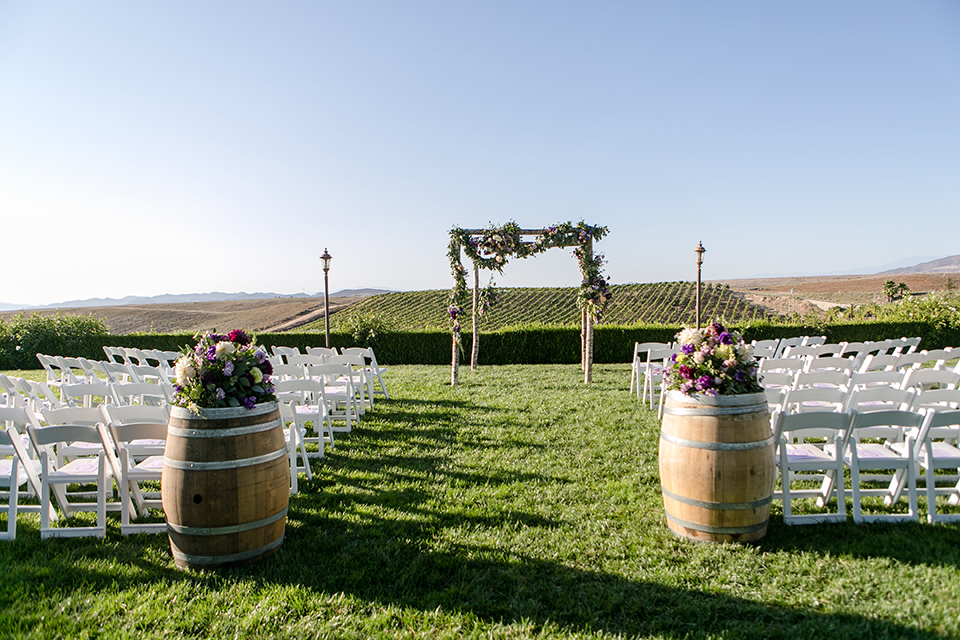 Temecula outdoor wedding at callaway winery ceremony set up on grass with wooden arch and white chairs with purple and white flower decor and wine barrels