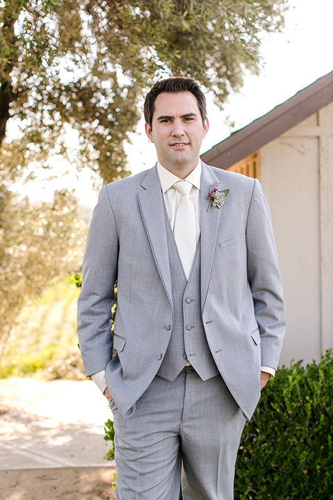Temecula outddor wedding at callaway winery groom heather grey suit with matching vest and white dress shirt with long ivory tie and purple floral boutonniere