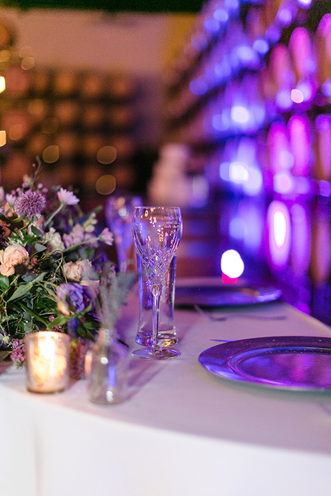 Temecula outdoor wedding at callaway winery table set up with white table linen and purple napkin linen decor with dark chairs and white and purple flower centerpiece decor with silver place settings with heart decor and candles