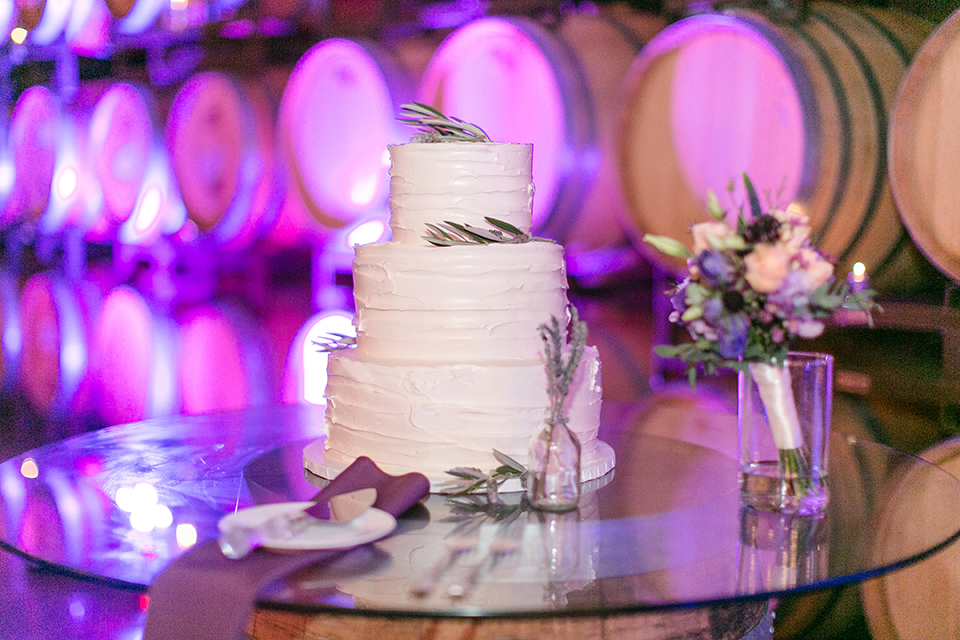 Temecula outdoor wedding at callaway winery table set up with white table linen and purple napkin linen decor with dark chairs and white and purple flower centerpiece decor with silver place settings with heart decor and candles with three tier white wedding cake with flower decor