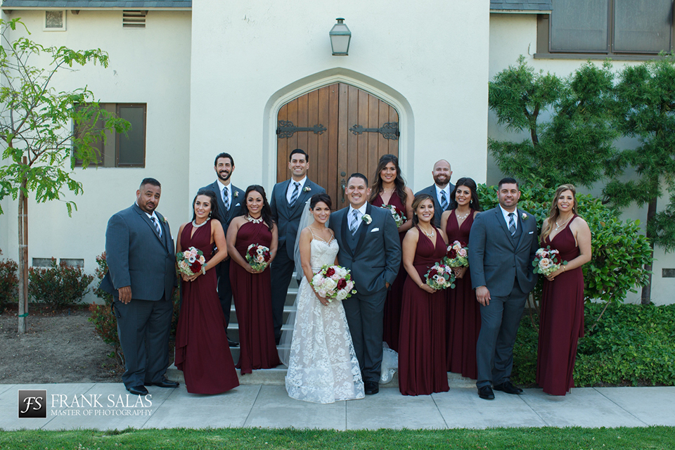 Long beach burgundy wedding at the loft on pine groom charcoal grey tuxedo with black shawl lapel and matching vest with white dress shirt and long plaid tie with groomsmen charcoal grey suits with matching vests and white dress shirts with long plaid ties and white floral boutonnieres with bride ball gown with thin straps and beaded bodice with lace detail and bridesmaids long burgundy dresses with white and burgundy floral bridal bouquets