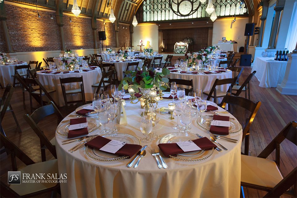 Long beach burgundy wedding at the loft on pine reception table set up with gold table linen and burgundy napkin decor with white place settings and white and green flower centerpiece decor with glasses and dark chairs