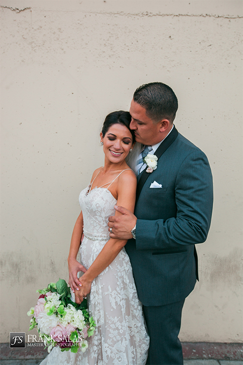 Long beach burgundy wedding at the loft on pine bride ball gown with thin beaded straps and sweetheart neckline with beaded detail on bodice with white and burgundy floral bridal bouquet with groom charcoal grey tuxedo with black shawl lapel and matching vest with white dress shirt and long plaid tie with white pocket square and white floral boutonniere hugging