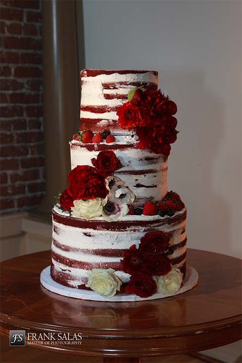 Long beach burgundy wedding at the loft on pine wedding cake three tier white and red naked wedding cake with dark red and white flowers on side and on top sitting on white tray on dark brown wood table wedding photo idea for cake