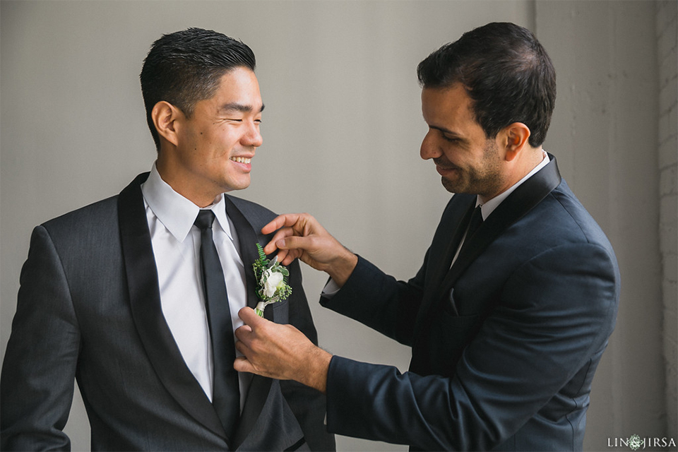 Downtown los angeles wedding groom charcoal grey tuxedo with black shawl lapel and white dress shirt with long black skinny tie with white floral boutonniere getting ready