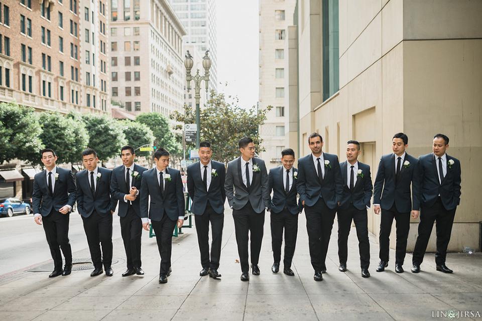Downtown los angeles wedding groom and groomsmen charcoal grey tuxedos with black shawl lapel and black pants with white dress shirt and long black skinny tie with white floral boutonniere walking