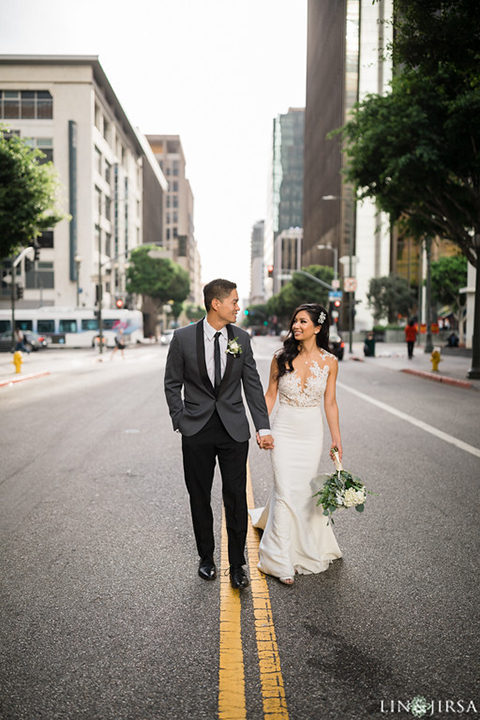 Downtown los angeles wedding bride form fitting lace gown with illusion back and high neckline with crystal hair piece with groom charcoal grey tuxedo with black shawl lapel and white dress shirt with long black skinny tie and white floral boutonniere walking in the street holding hands