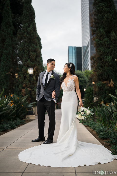 Downtown los angeles wedding bride form fitting lace gown with illusion back and high neckline with crystal hair piece with groom charcoal grey tuxedo with black shawl lapel and white dress shirt with long black skinny tie and white floral boutonniere bride holding white floral bouquet