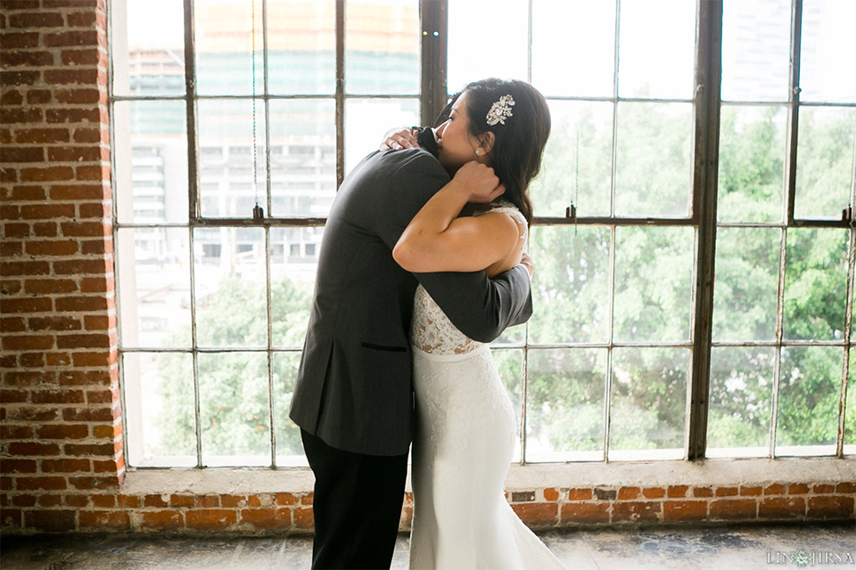 Downtown los angeles wedding bride form fitting lace gown with illusion back and high neckline with crystal hair piece with groom charcoal grey tuxedo with black shawl lapel and white dress shirt with long black skinny tie and white floral boutonniere hugging after first look
