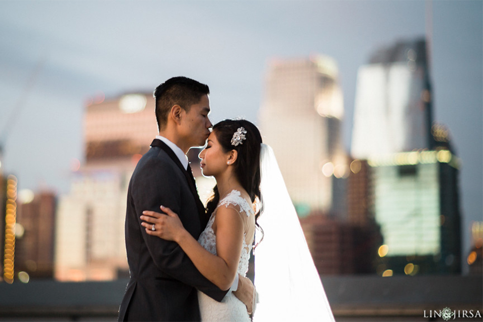 Downtown los angeles wedding bride form fitting lace gown with illusion back and high neckline with crystal hair piece with groom charcoal grey tuxedo with black shawl lapel and white dress shirt with long black skinny tie and white floral boutonniere hugging