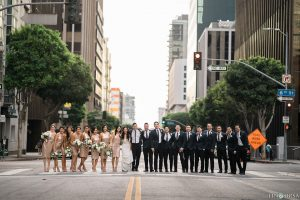 Downtown los angeles wedding bride form fitting lace gown with illusion back and high neckline with crystal hair piece with groom charcoal grey tuxedo with black shawl lapel and white dress shirt with long black skinny tie and white floral boutonniere with bridesmaids short gold sequined dresses and groomsmen black tuxedos with long black skinny ties