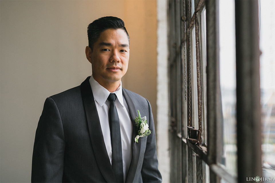 Downtown los angeles wedding groom charcoal grey tuxedo with black shawl lapel and black pants with white dress shirt with long black skinny tie and white floral boutonniere