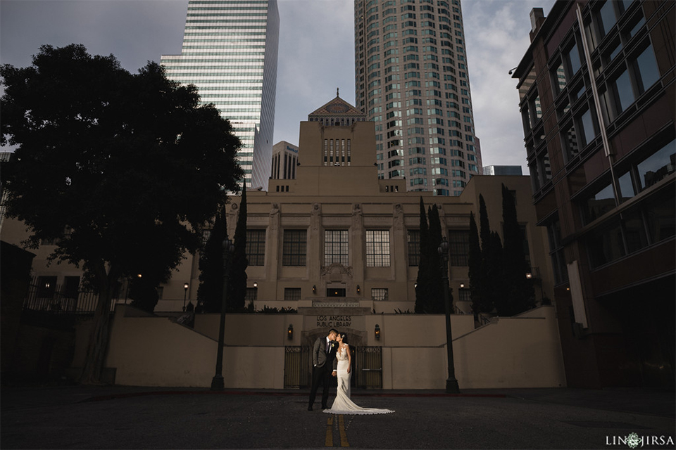 Downtown los angeles wedding bride form fitting lace gown with illusion back and high neckline with crystal hair piece with groom charcoal grey tuxedo with black shawl lapel and white dress shirt with long black skinny tie and white floral boutonniere hugging outside building