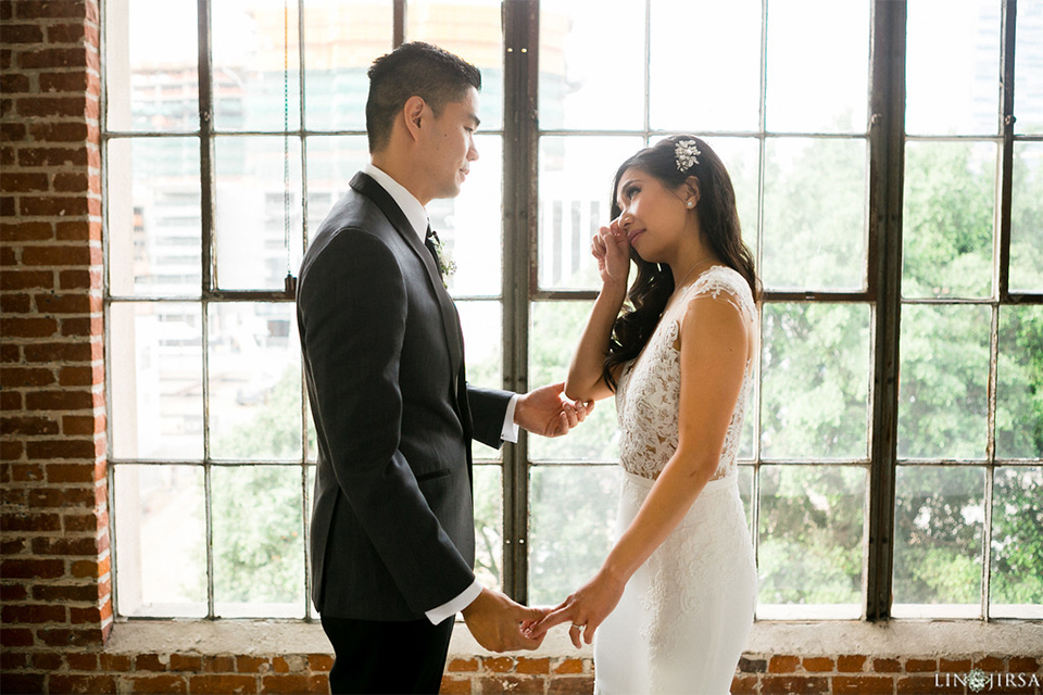 Downtown los angeles wedding bride form fitting lace gown with illusion back and high neckline with crystal hair piece with groom charcoal grey tuxedo with black shawl lapel and white dress shirt with long black skinny tie and white floral boutonniere crying after first look