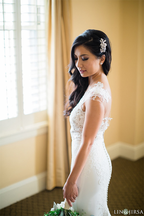 Downtown los angeles wedding bride form fitting lace gown with illusion back and high neckline with crystal hair piece wedding photo idea for bride holding white and green floral bridal bouquet