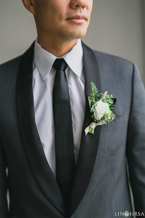 Downtown los angeles wedding groom charcoal grey tuxedo with black shawl lapel and black pants with white dress shirt with long black skinny tie and white floral boutonniere close up