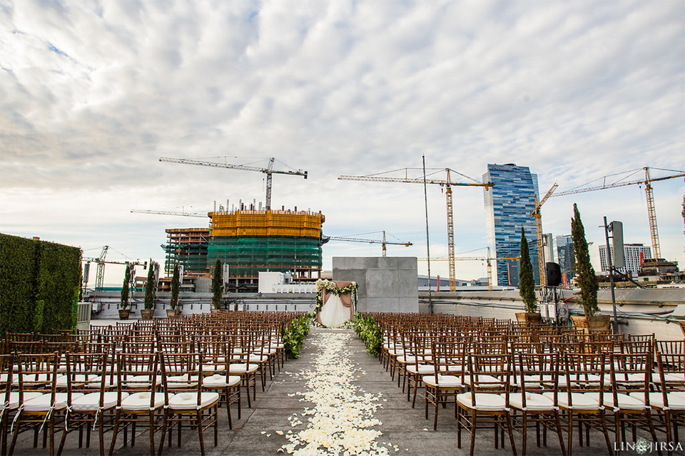 Downtown los angeles wedding ceremony set up with brown and white chairs with white flower petals on ground of rooftop with altar with white and green floral bridal bouquet wedding photo idea for ceremony