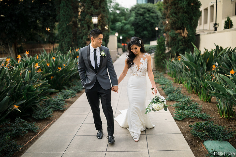 Downtown los angeles wedding bride form fitting lace gown with illusion back and high neckline with crystal hair piece with groom charcoal grey tuxedo with black shawl lapel and white dress shirt with long black skinny tie and white floral boutonniere walking and holding hands