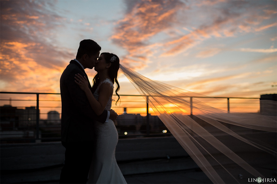 Downtown los angeles wedding bride form fitting lace gown with illusion back and high neckline with crystal hair piece with groom charcoal grey tuxedo with black shawl lapel and white dress shirt with long black skinny tie and white floral boutonniere kissing at sunset