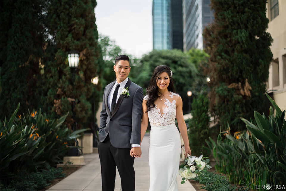 Downtown los angeles wedding bride form fitting lace gown with illusion back and high neckline with crystal hair piece with groom charcoal grey tuxedo with black shawl lapel and white dress shirt with long black skinny tie and white floral boutonniere holding hands and bride holding white and green floral bridal bouquet