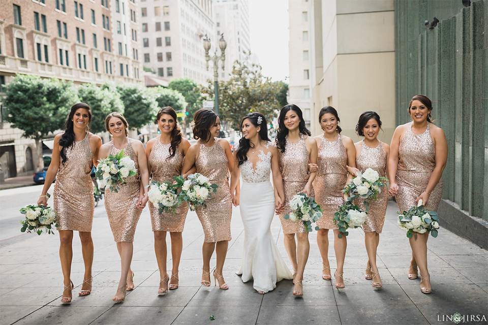 Downtown los angeles wedding bride form fitting lace gown with illusion back and high neckline with crystal hair piece with bridesmaids short gold sequined dresses holding white and green floral bridal bouquets walking