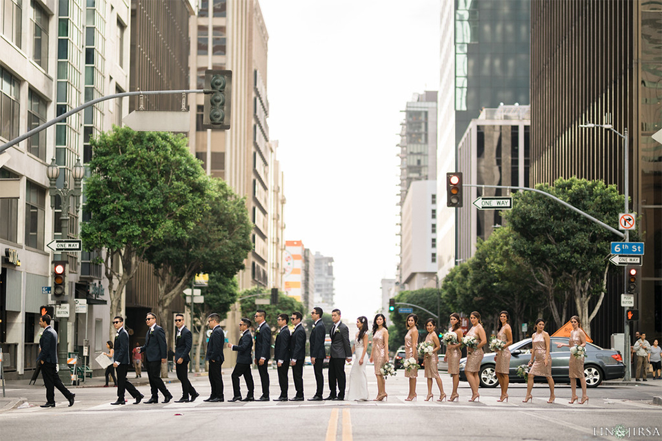 Downtown los angeles wedding bride form fitting lace gown with illusion back and high neckline with crystal hair piece with groom charcoal grey tuxedo with black shawl lapel and white dress shirt with long black skinny tie and white floral boutonniere with bridesmaids short gold sequined dresses and groomsmen charcoal grey tuxedos with black pants and long black skinny ties in middle of crosswalk in street