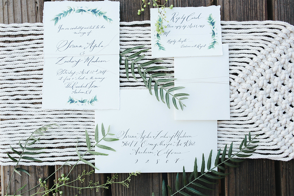 Orange county outdoor rustic wedding at the riverbed farm wedding invitations white with greenery floral and leaf decor with green calligraphy writing on dark brown wood background wedding photo idea for invitations