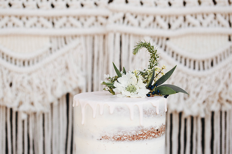 Orange county outdoor rustic wedding at the riverbed farm wedding cake two tier white naked design wedding cake with white and green flower decor on top with white lace background wedding photo idea for cake
