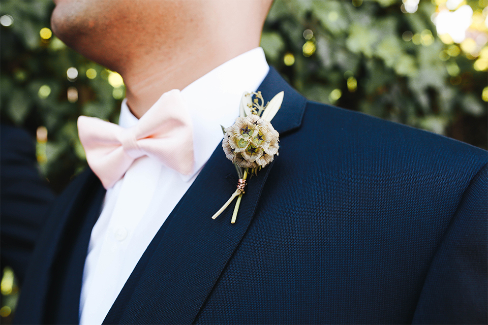 Orange county outdoor rustic wedding at the riverbed farm groom navy suit with white dress shirt and blush pink bow tie with white and green floral boutonniere and matching pocket square close up
