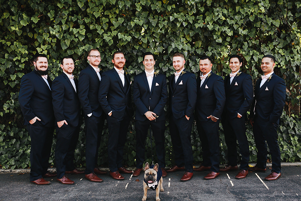 Orange county outdoor rustic wedding at the riverbed farm groom navy suit with white dress shirt and blush pink bow tie with white and green floral boutonniere and matching pocket square with groomsmen navy blue suits with blush pink bow ties and dog standing in front of them