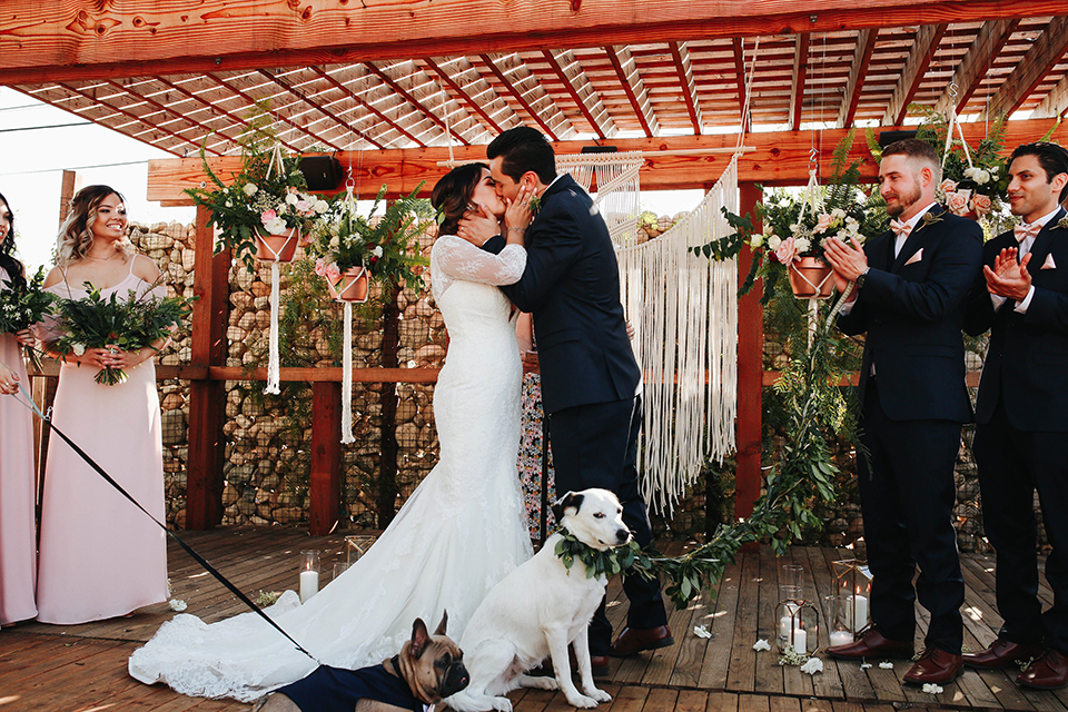 Orange county outdoor rustic wedding bride form fitting lace gown with sleeves and plunging neckline with groom navy blue notch lapel suit with white dress shirt and blush pink bow tie with matching pocket square and whit and green floral boutonniere kissing during ceremony