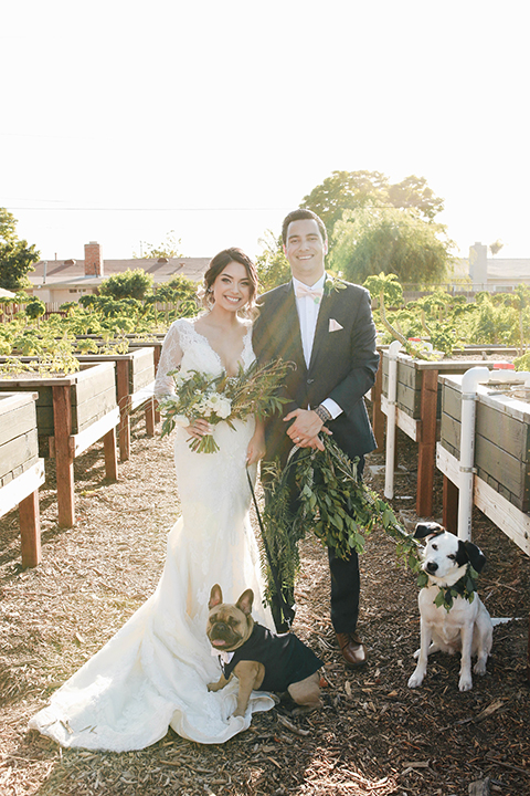 Orange county outdoor rustic wedding bride form fitting lace gown with sleeves and plunging neckline with groom navy blue notch lapel suit with white dress shirt and blush pink bow tie with matching pocket square and whit and green floral boutonniere standing with dog